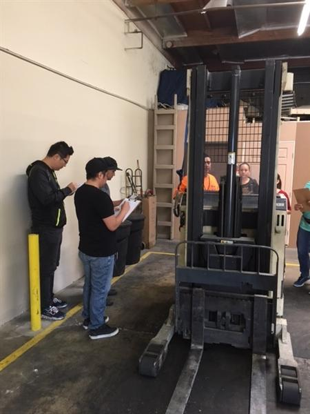 Students taking notes on fork lift