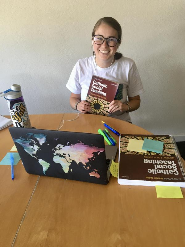 teacher looking at camera at table with laptop and books