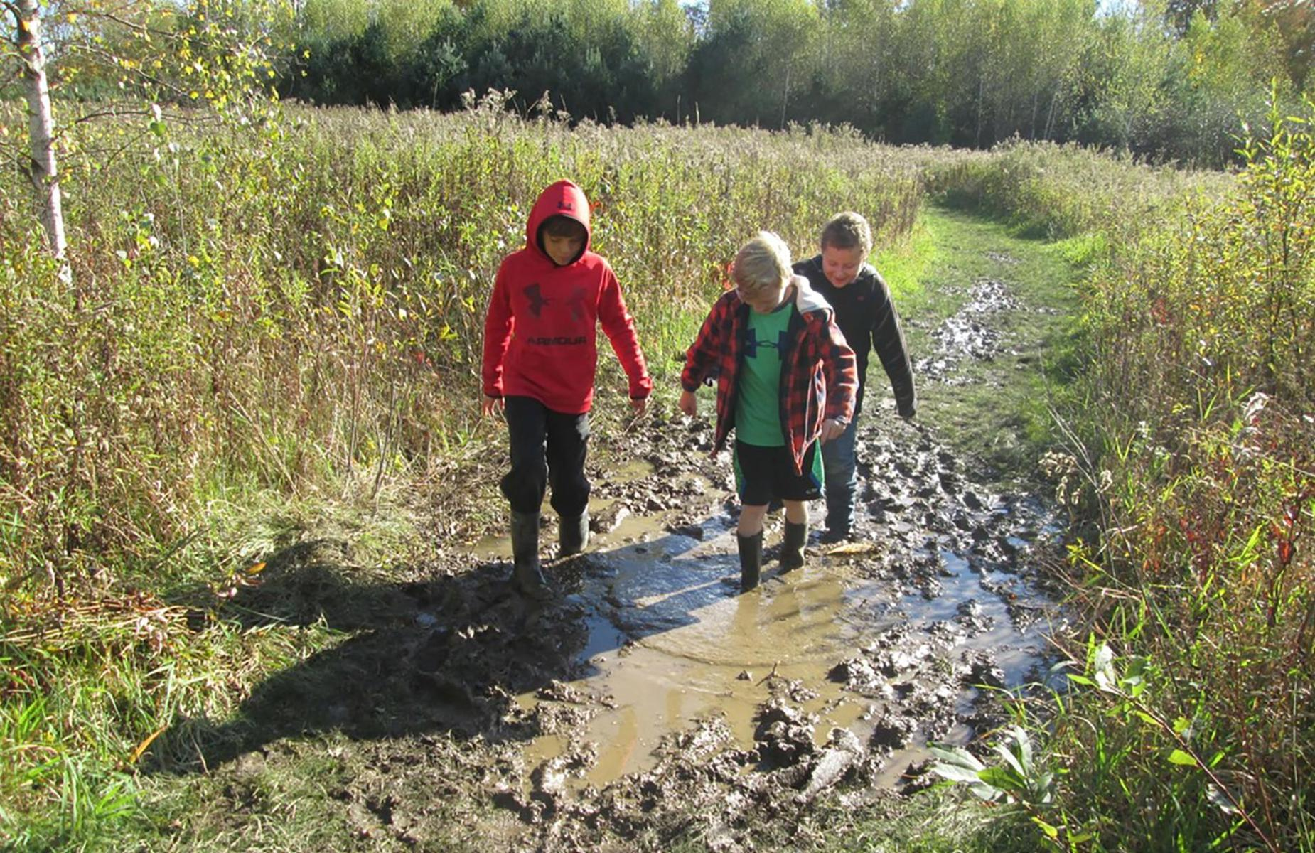 3 students walking through mud