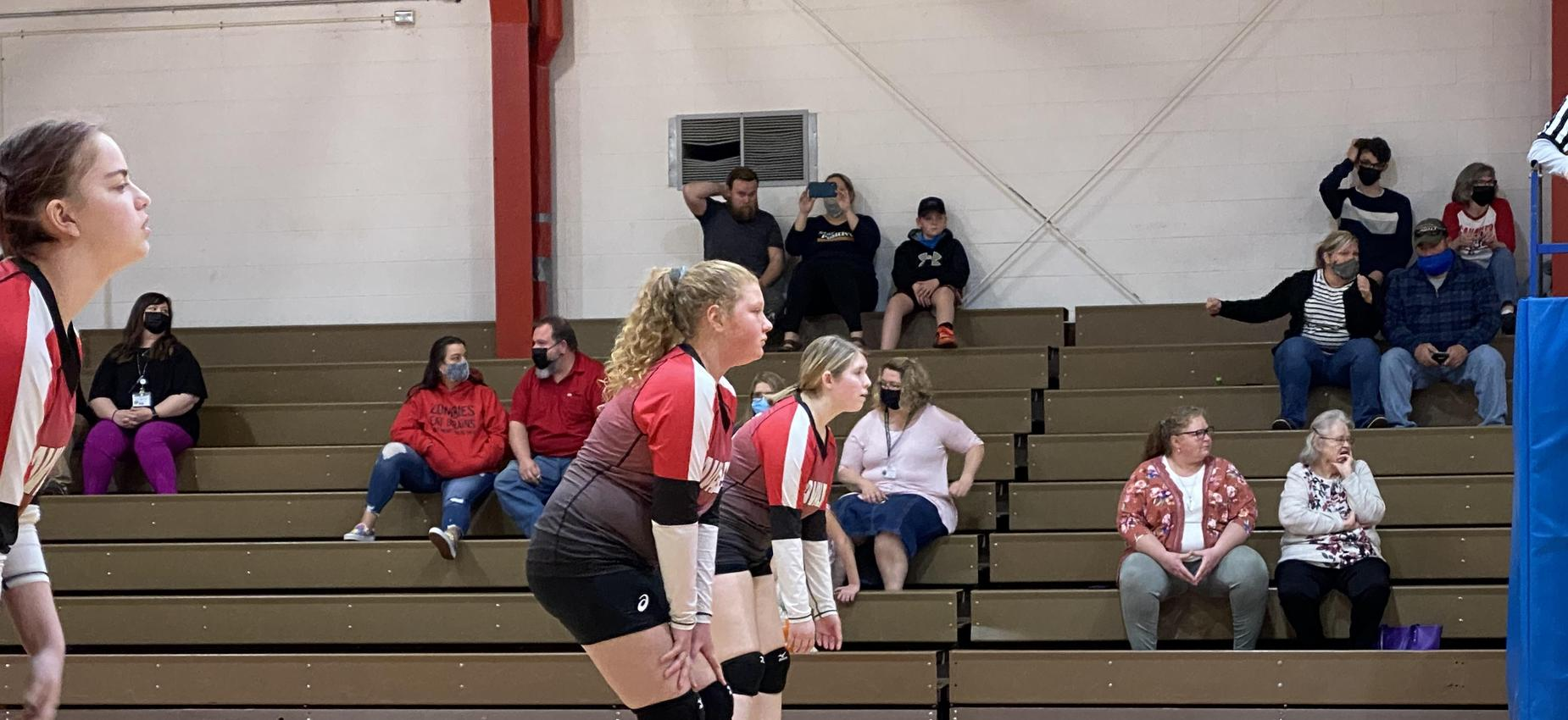 Two volleyball players wait for a serve.