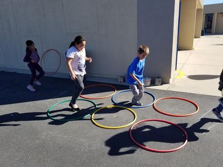 Students hoping on one leg over Hula Hoops