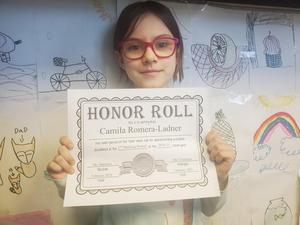 Camila holding honor roll certificate