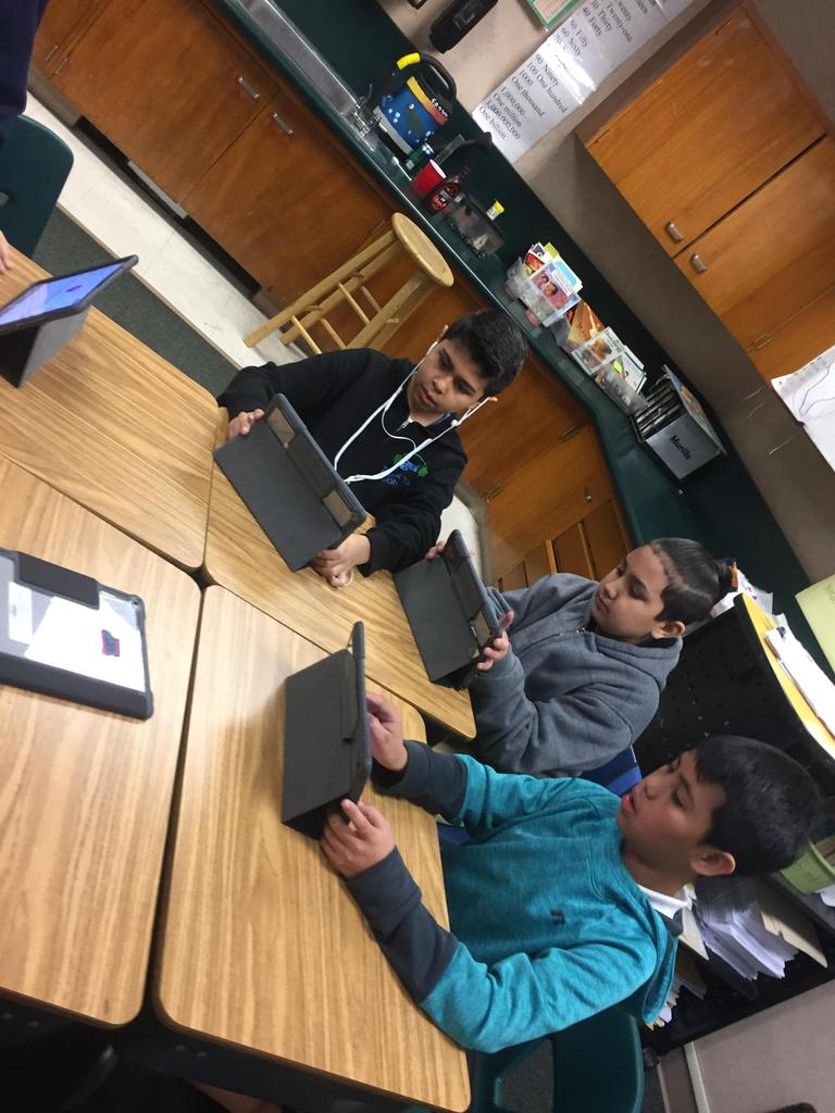 students in table group working on coding on iPads