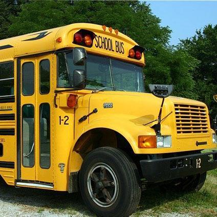 Front passenger side view of yellow school bus.
