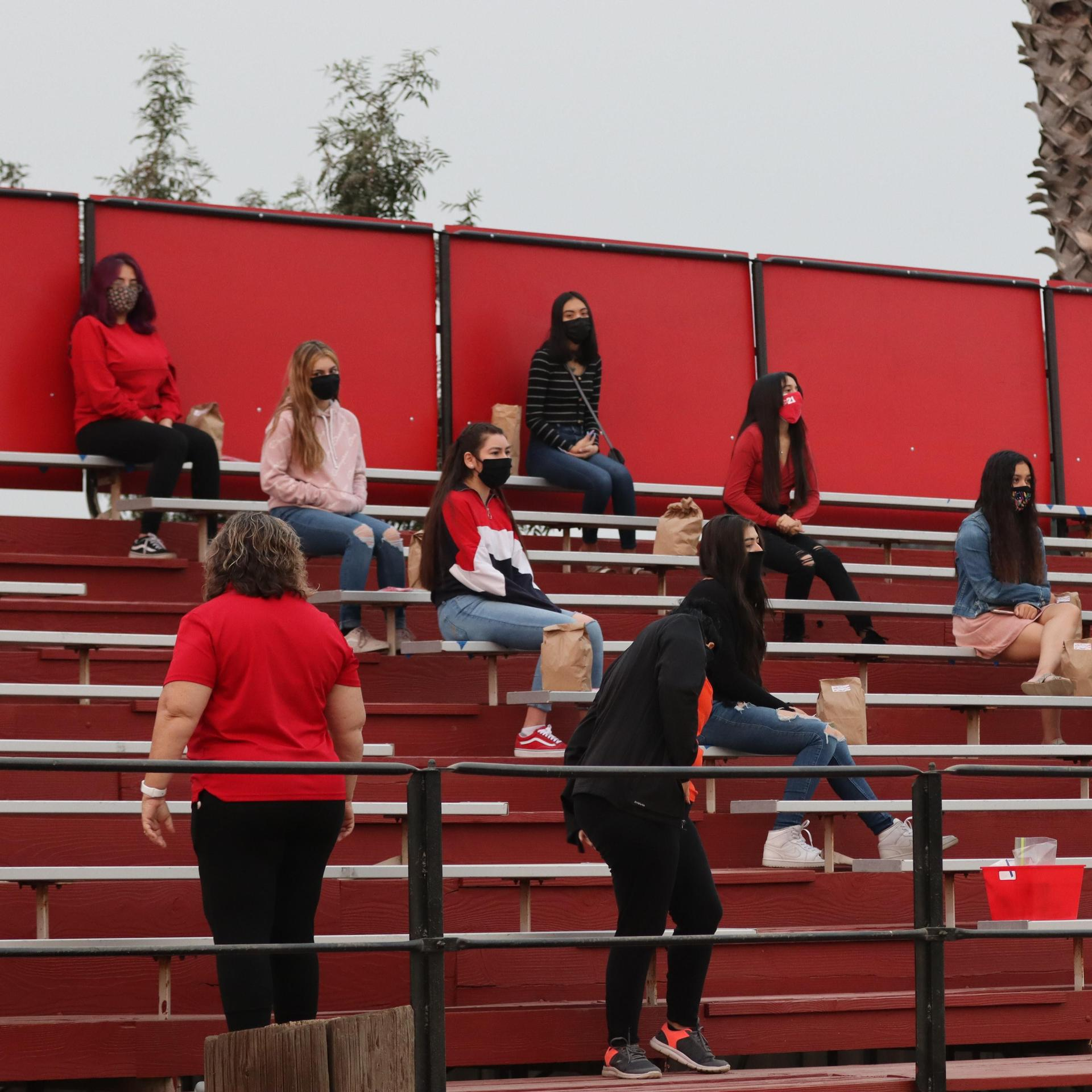 students and staff sitting in the bleachers