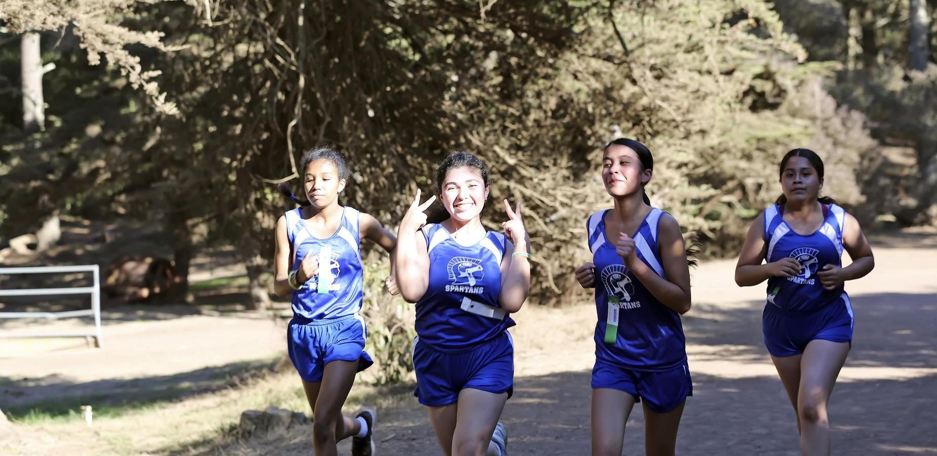 Four Spartan Cross Country Runners during meet saying Hi!