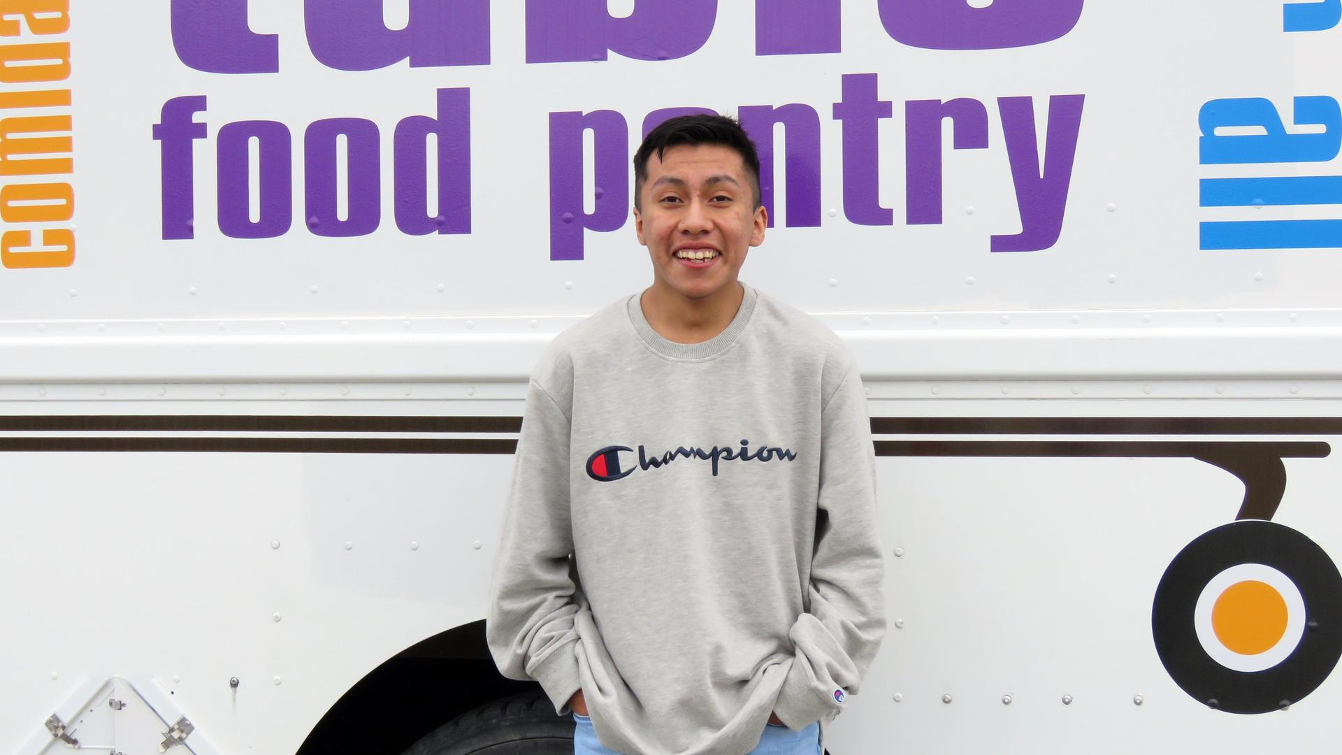 A teen boy stands in front of the Traveling Pantry mobile food truck