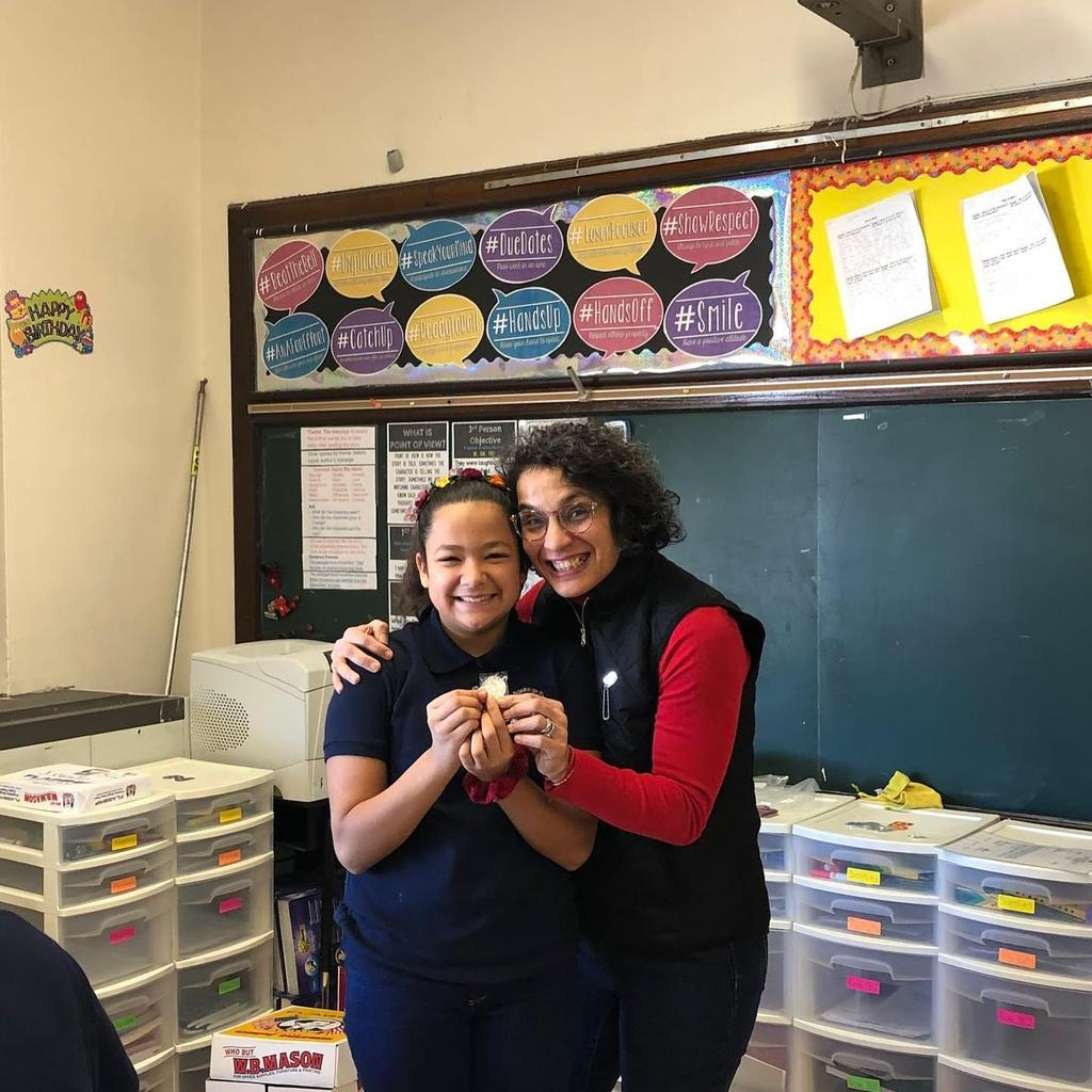 Melanie holding up her Challenge coin with Lucy Del Gaudio