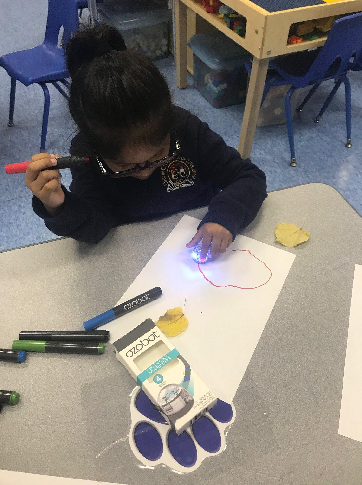 Little girl with an ozobot coding tools creating a drawing
