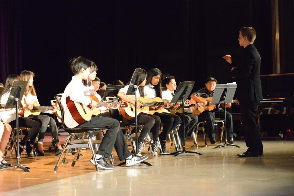 Music teacher conducts CCA's band.