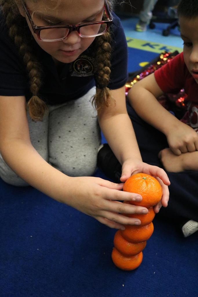 girl stacking tangerines