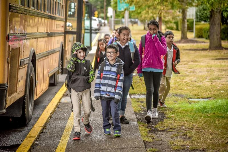 Group of students walking into school past a school bus
