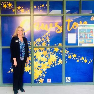 Donna Arias standing in front of a Cawston window cling.