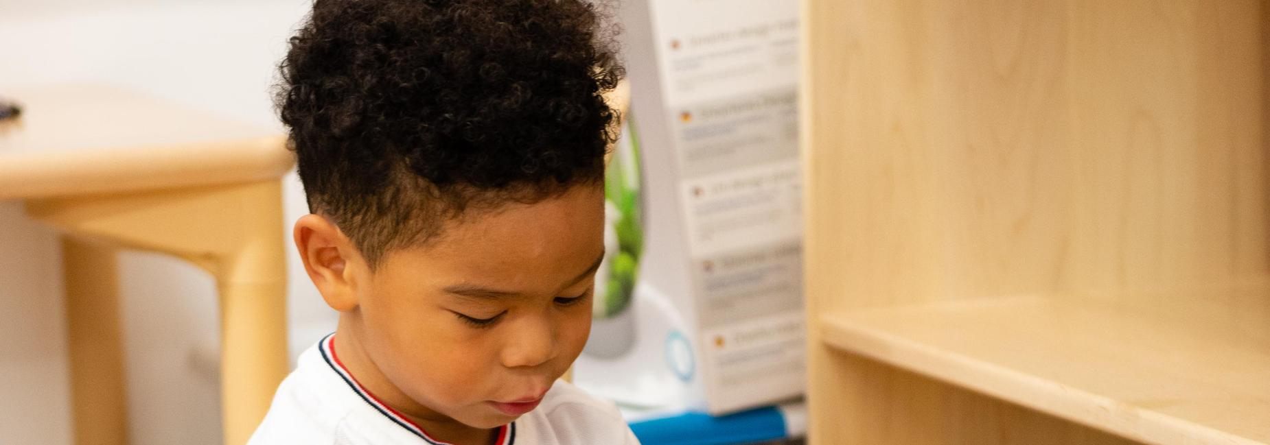 A pre-k student seated in front of a bookshelf.