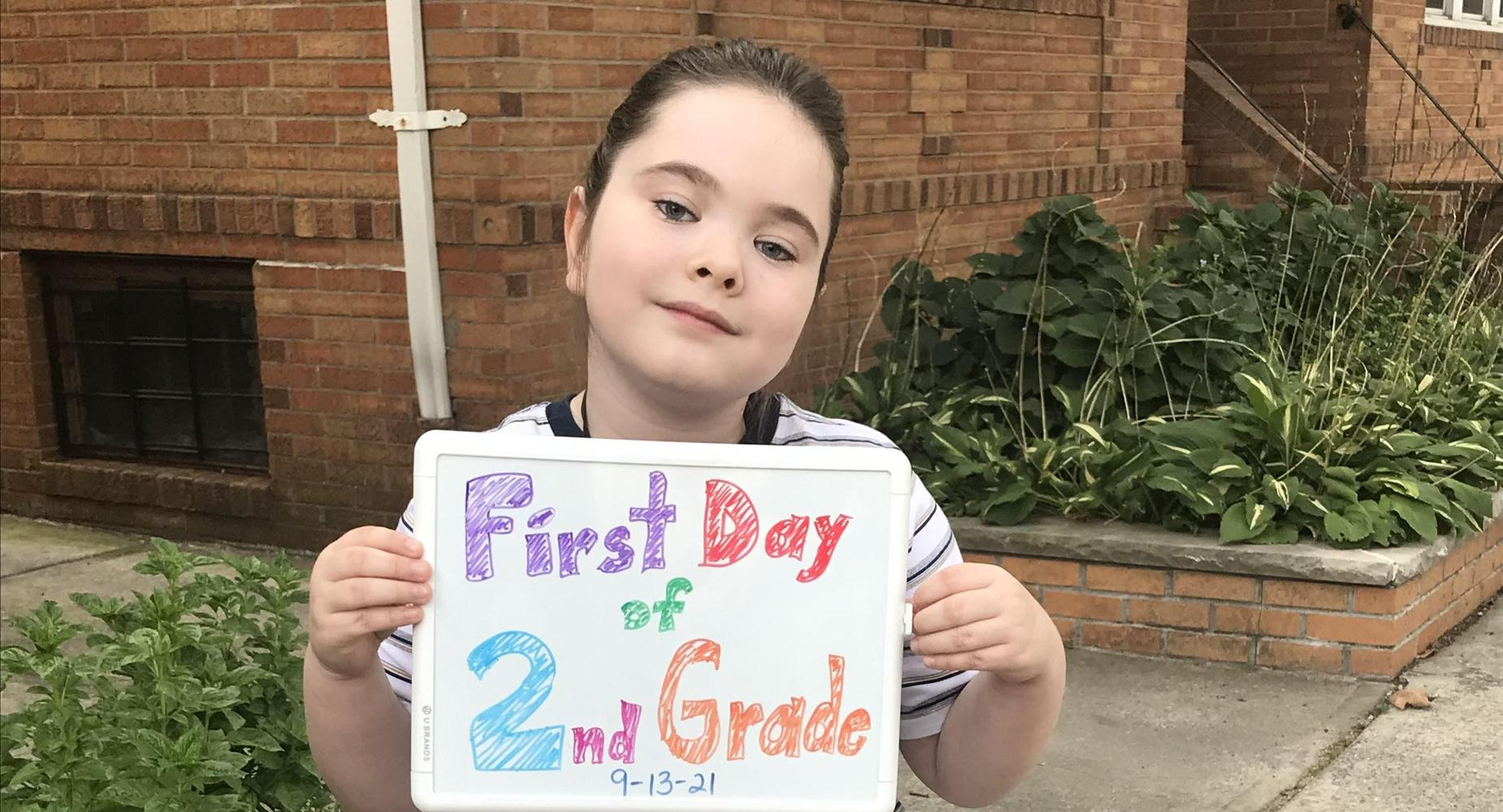 boy holding first day of second grade sign