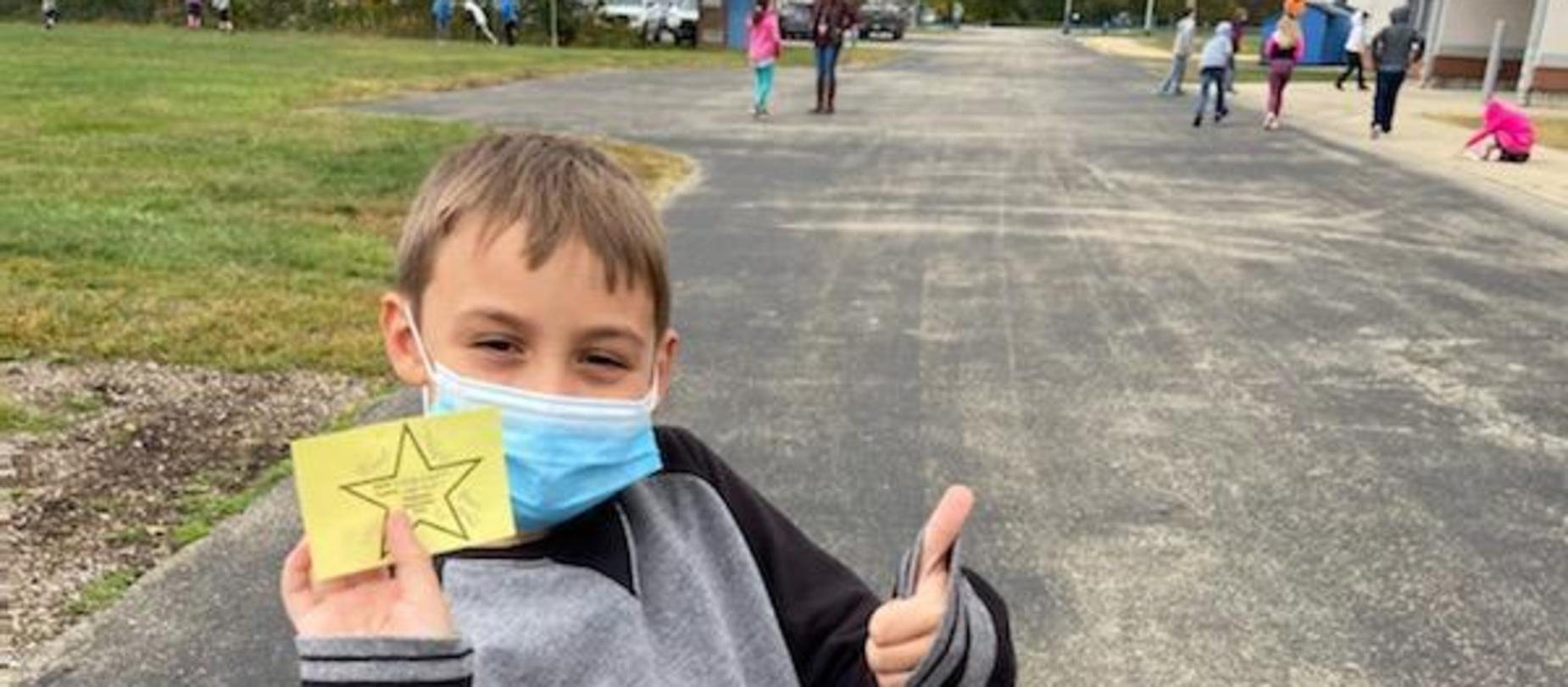 boy outside wearing a mask, giving a thumbs up