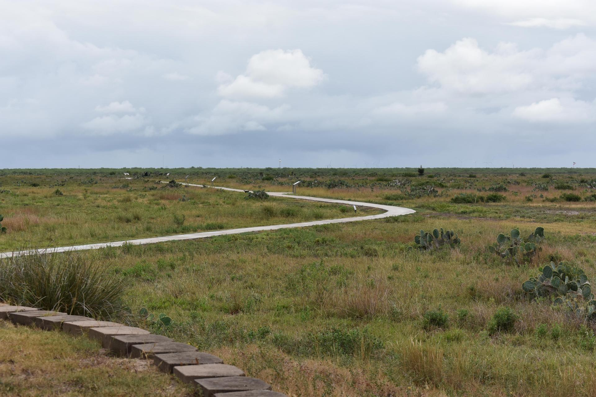 Trail going through flat grassland