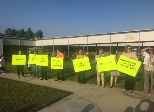 Teachers holding positive signs