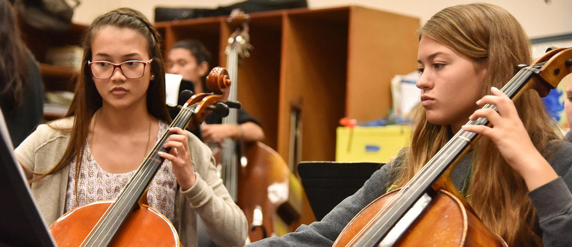 Two students playing the cello