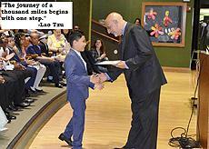 """The journey of a thousand miles begins with one step."" - Lao Tzu   Image of a young student walking up to get his 6th grade diploma"