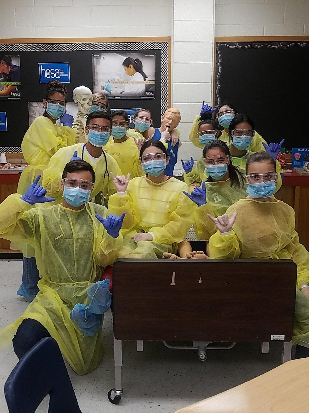 students in health class taking group picture wearing face mask, gloves and apron