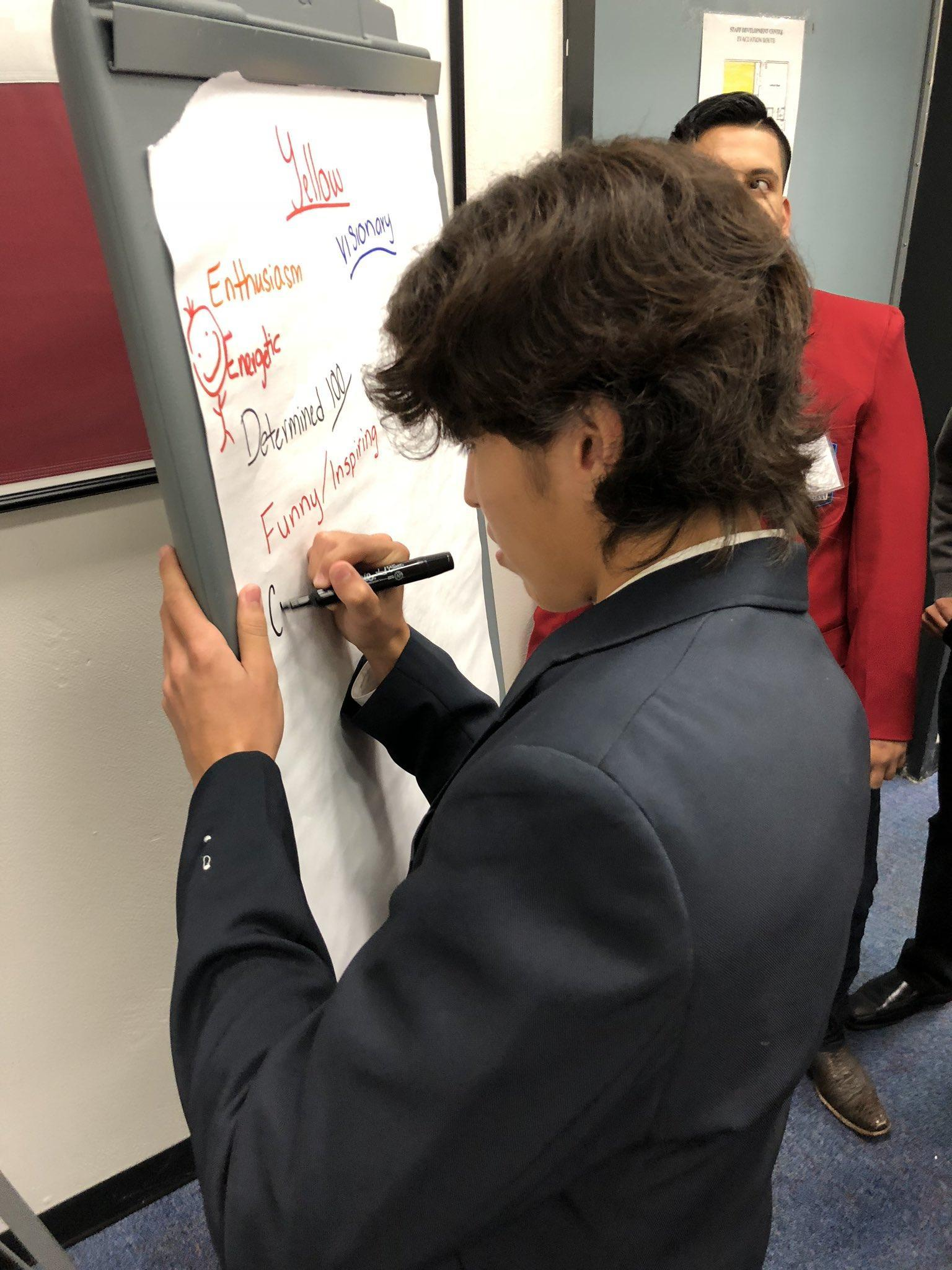 student in suit writing on paper
