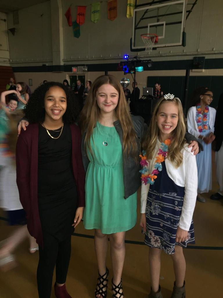 Three diverse students smiling at Daddy-Daughter Dance