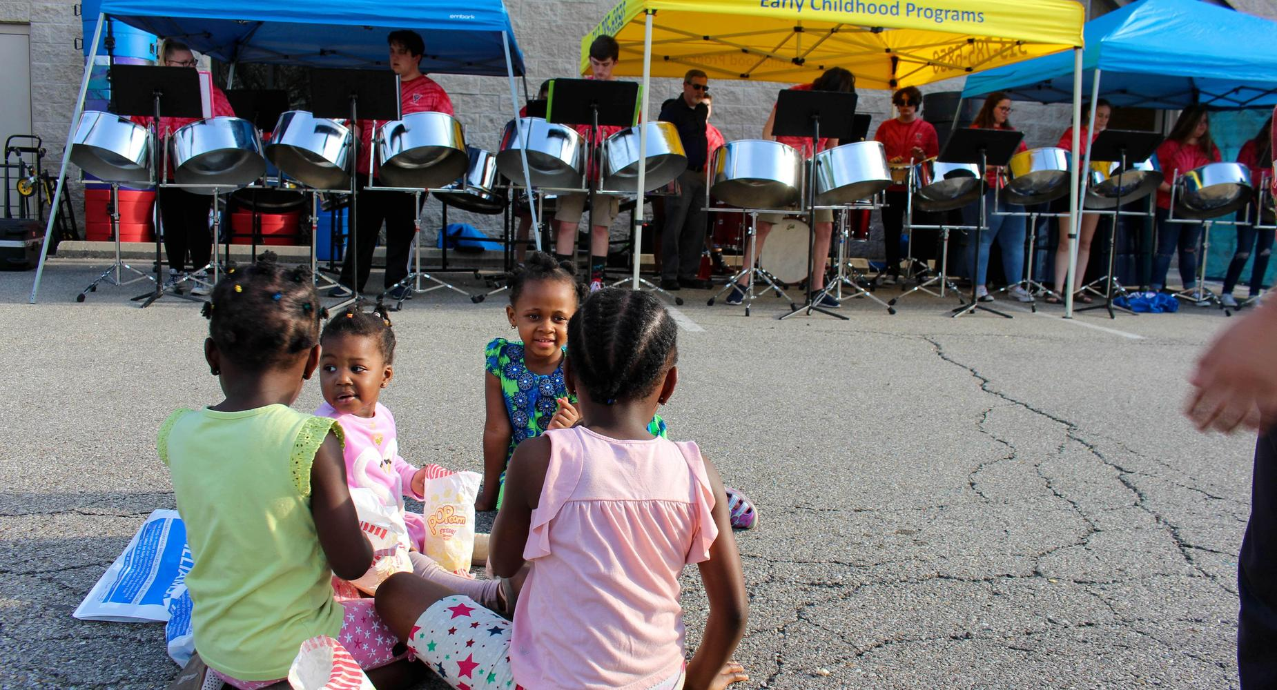 Four Black female children ages 3-5 snack on popcorn in front of a steel drum band at the Friends Around the World cultural celebration