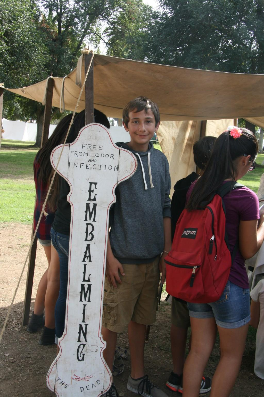 TLR student next to sign