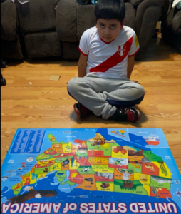 Boy sitting on floor behind USA map puzzle