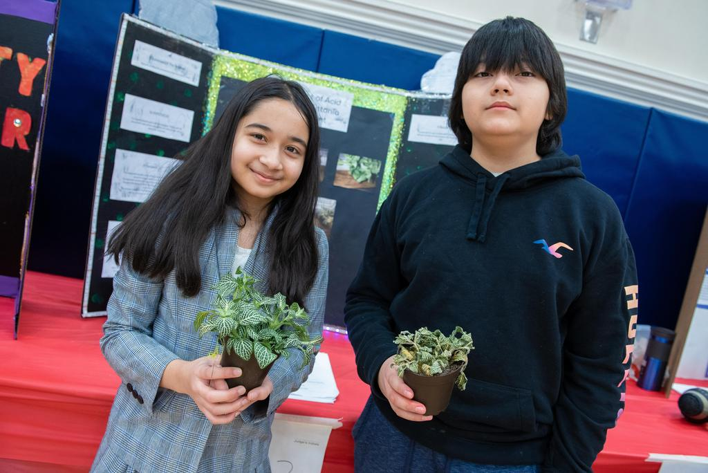 Two students hold small pots of plants