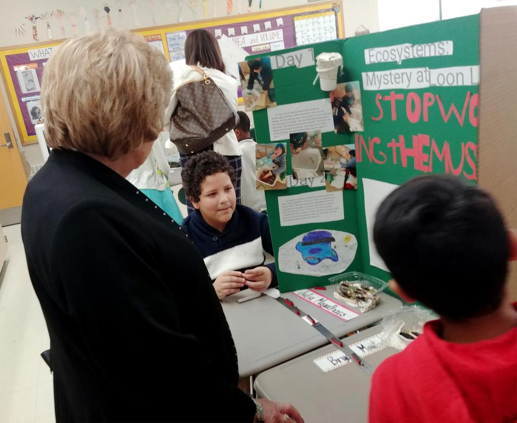 Two students talk to Superintendent Janice Gauthier about their STEM project