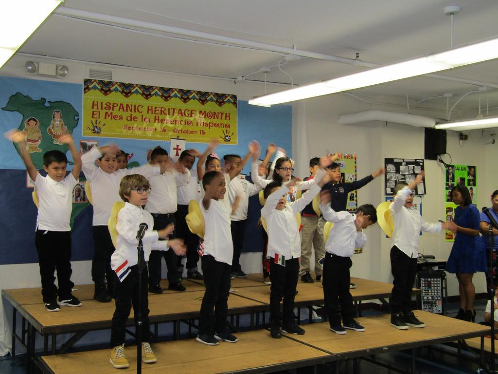 group of girls and boys on stage singing with their hands up in the air