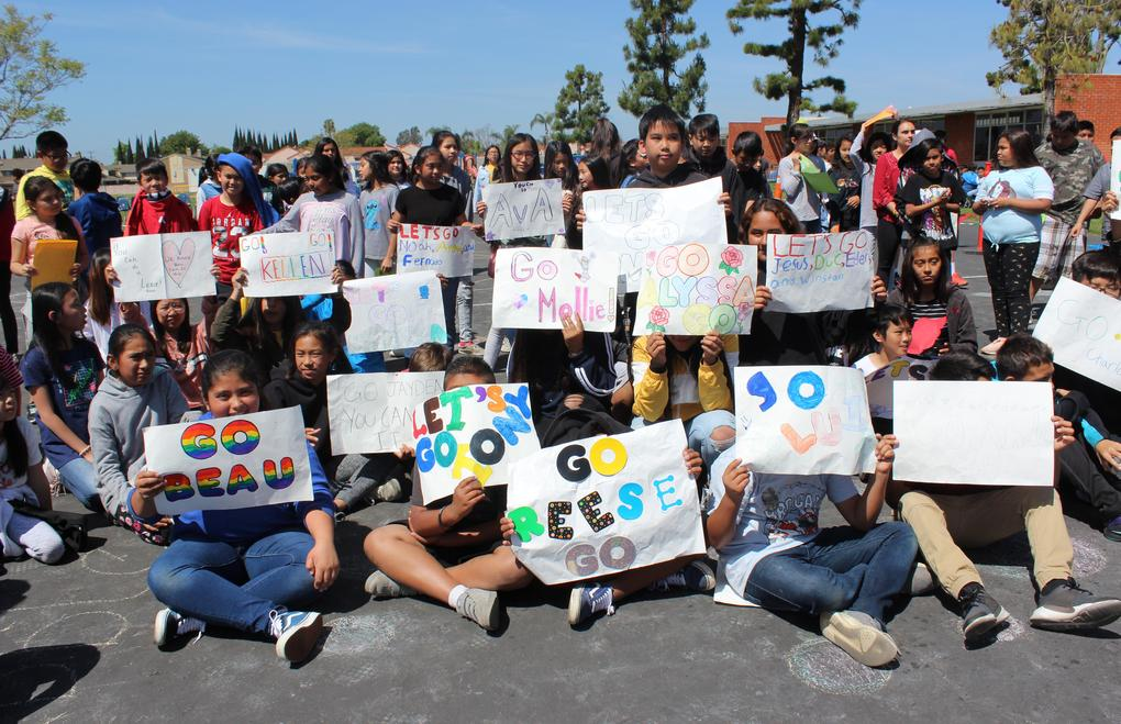Students hold signs in support of Special Olympics participants.