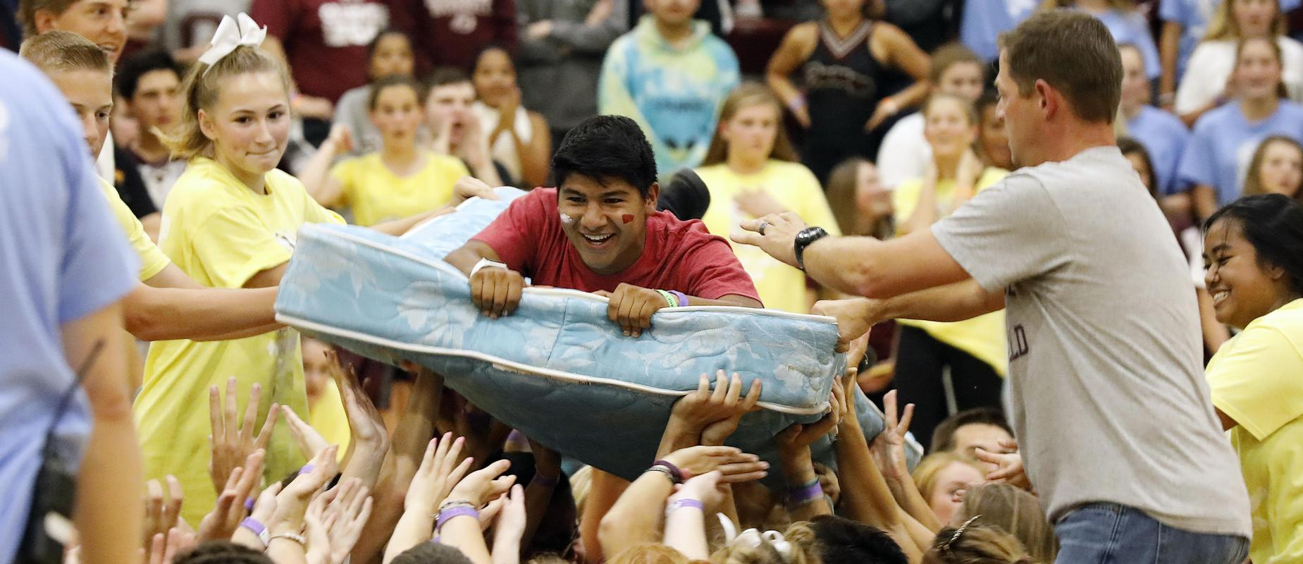 boy in mattress relay floats across gym with help of classmates