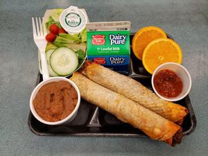 Picture of student lunch tray featuring crispitos, beans, salsa, salad, fruit and milk.