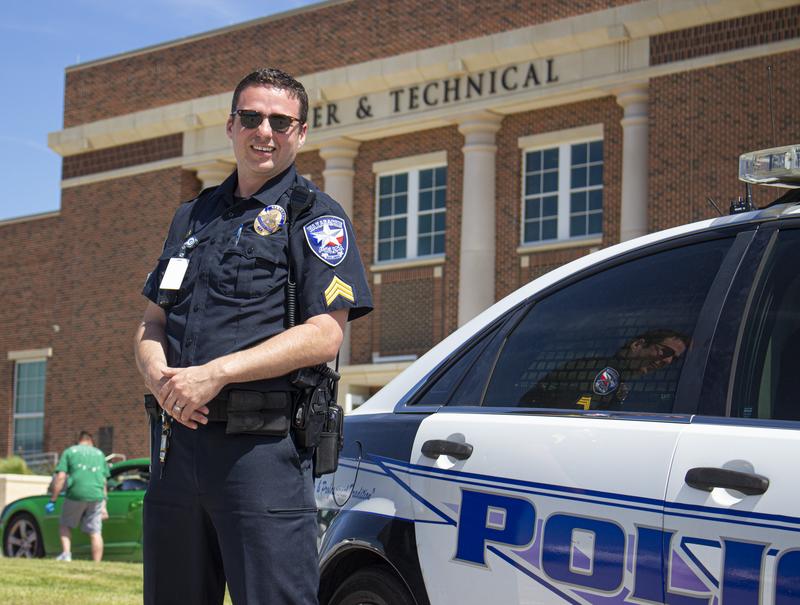 uniformed officer posing beside squad car
