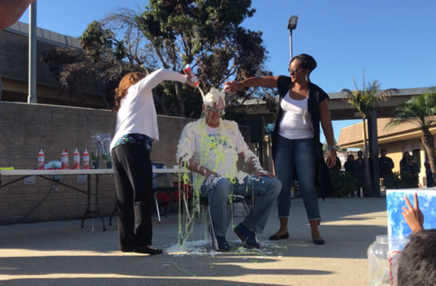 Two female teacher putting whip cream on the principals head