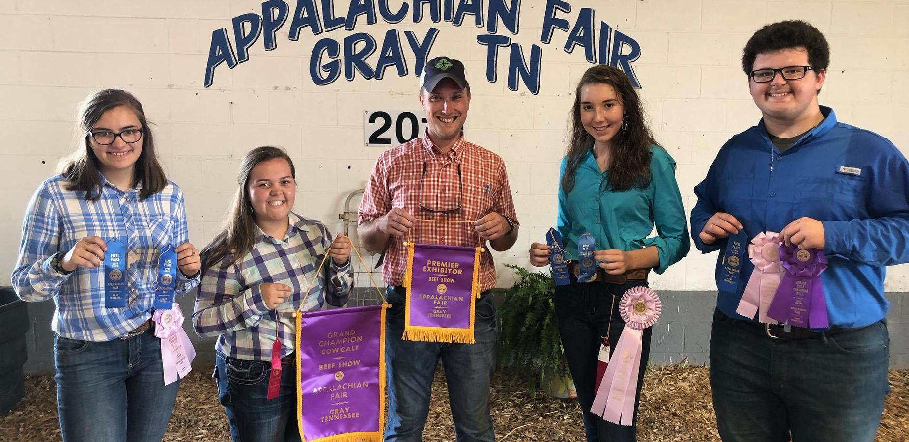FFA students holding awards from cattle show