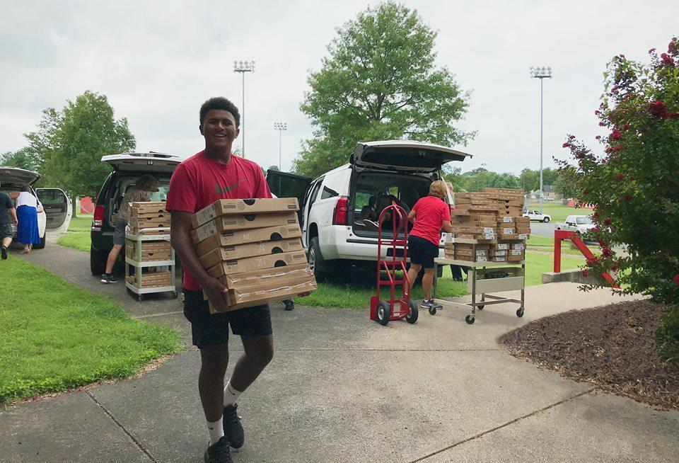 Picture of student carrying in Chromebooks to Mayfield High School for the one to one initiative that started during the 2018-2019 school year
