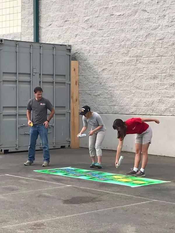 Volunteers spray paint a hopscotch game at Snake River Elementary.