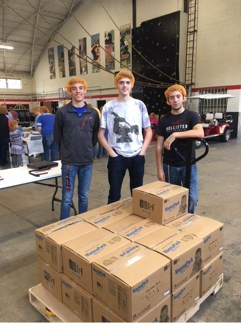 Three Beta Club students in front of a food pallet