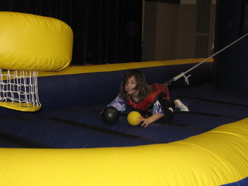 girl in harness playing on inflatable mat