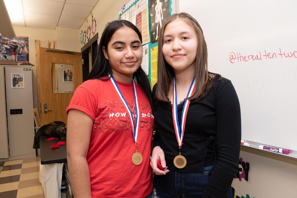 Two students wearing their honorable-mention medals