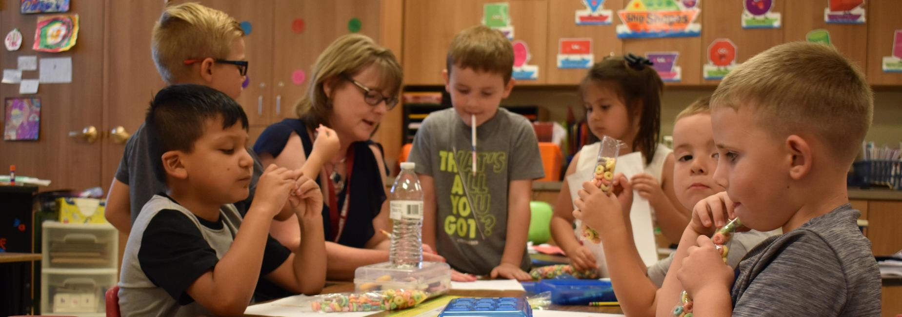 Students and teacher gather around table during snack time