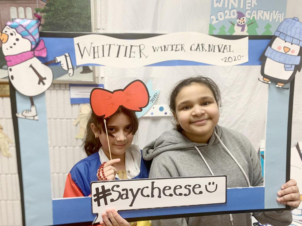 Two young students at the photo booth featuring a handmade, winter-themed frame