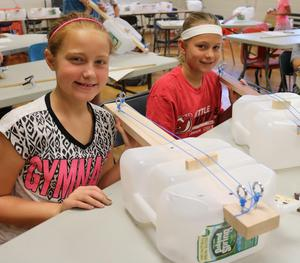 Two STEM campers display musical instruments they built out of recycled materials during STEM Camp.