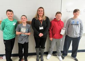Page 5th graders present donations to a local charity.