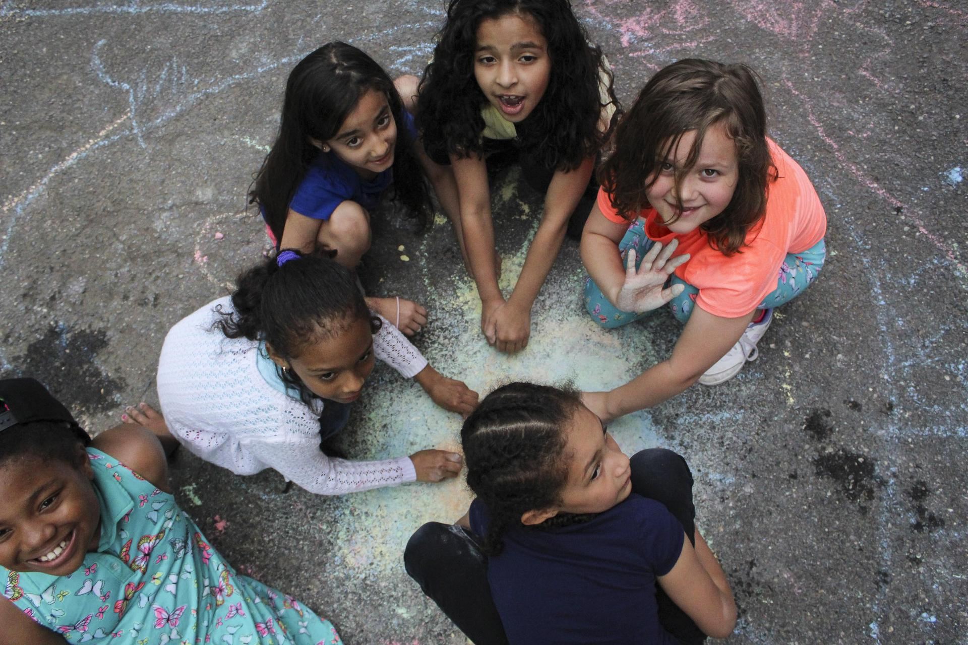 Group of students drawing on pavement with chalk