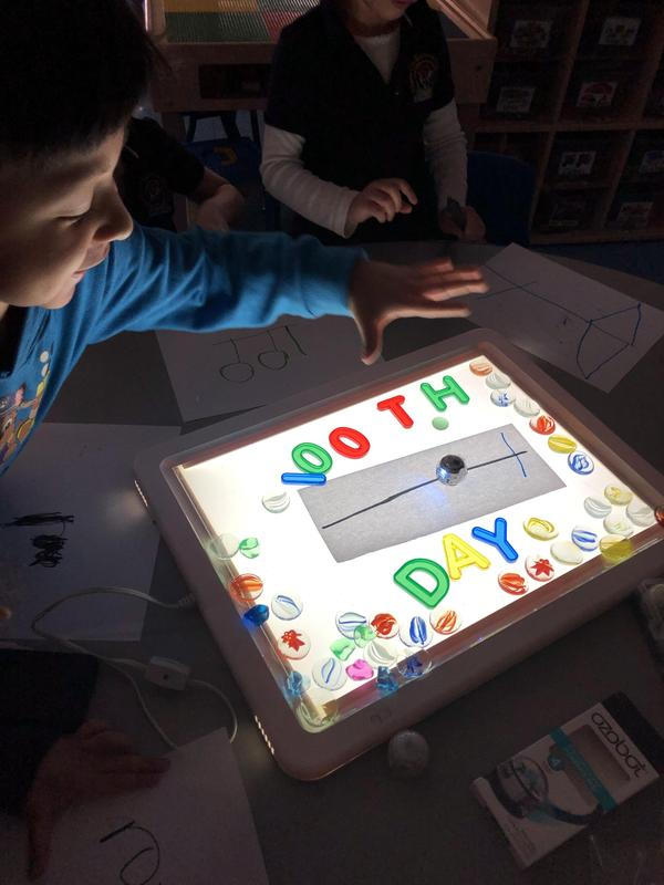 a boy and a girl with a lit programming board that says 100th day